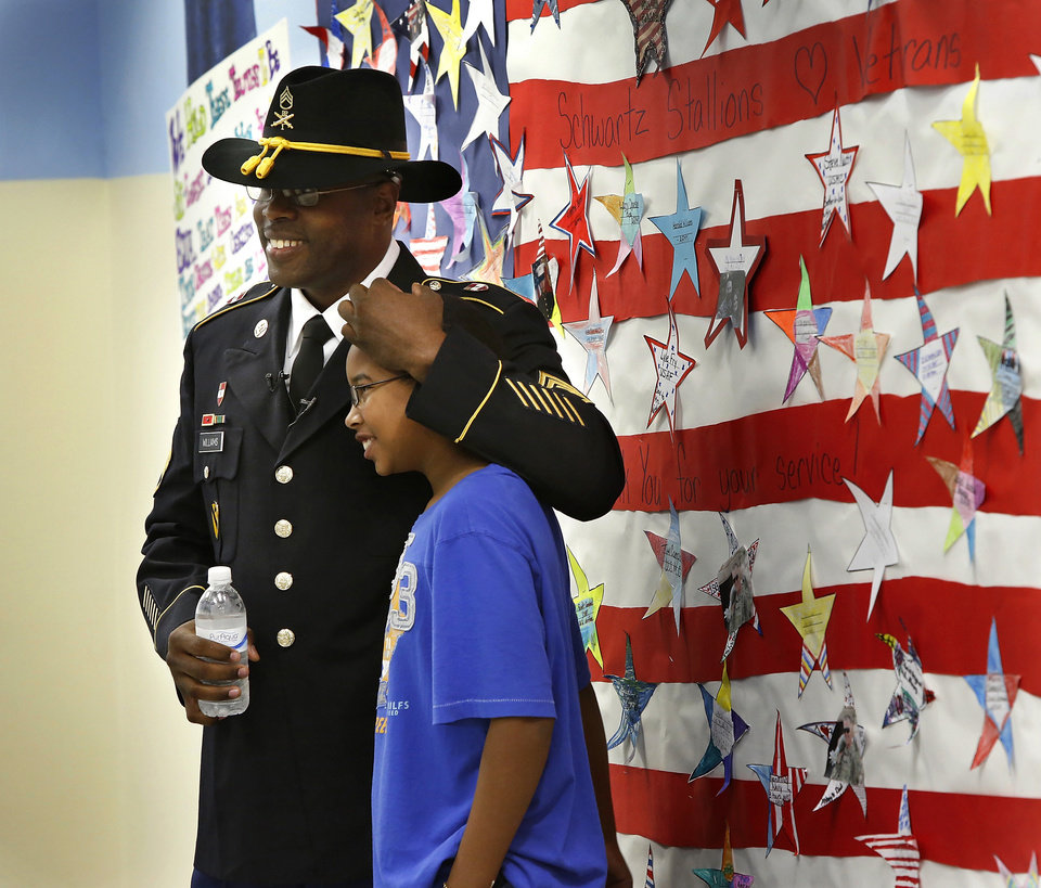 Staff Sergeant Harold Williams poses for a picture with his son in front of a bulletin board dedicated to active military families and veterans related to students and faculty at Schwartz School. Williams urprised his son, Adrian, a fifth grade student during a patriotic-themed Veteran's Day assembly Friday morning, Nov. 9, 2012, at Schwartz Elementary School, when he walked onto the stage while his son and classmates were reciting the preamble of the U.S. Constitution.  The elder Williams arrived at the school this morning and had been hidden off stage until his son's class gathered on the stage. Father and son embraced for nearly two minutes in front of a large red, white and blue backdrop. Adrian wiped away tears and tears also rolled down the cheeks of Sgt. Williams.  Harold has been stationed in Germany with the U.S. Army and recently returned there from duty in Iraq.      Photo by Jim Beckel, The Oklahoman