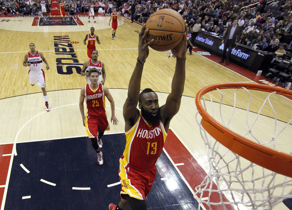 Houston Rockets guard James Harden (13) dunks, with forward Chandler Parsons (25) following, in the first half of an NBA basketball game against the Washington Wizards, Saturday, Feb. 23, 2013, in Washington. (AP Photo/Alex Brandon)