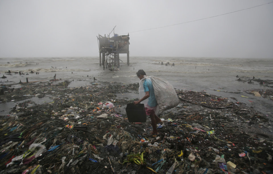 Photo - A Filipino man scavenges recyclable materials by the bay as strong winds and rains caused by Typhoon Koppu hit the coastal town of Navotas, north of Manila, Philippines on Sunday, Oct. 18, 2015.  Slow-moving Typhoon Koppu blew ashore with fierce wind in the northeastern Philippines early Sunday, toppling trees and knocking out power and communications. (AP Photo/Aaron Favila)