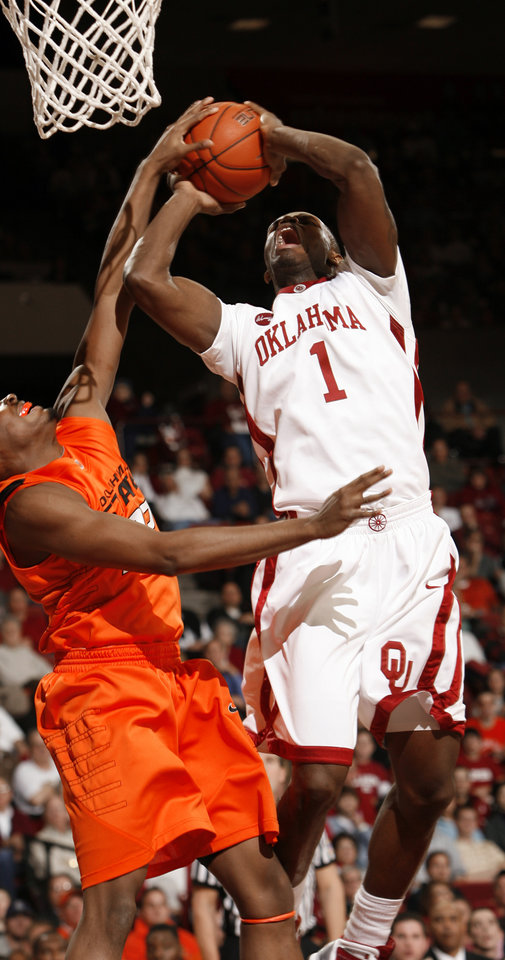 Photo - Ryan Wright (1) is fouled by Roger Franklin (32) during the first half of the college bedlam basketball game between The University of Oklahoma Sooners (OU) and Oklahoma State University University Cowboys (OSU) at the Lloyd Noble Center on Monday, Jan. 11, 2010, in Norman, Okla.