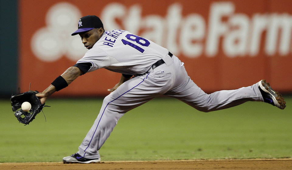 Photo -   Colorado Rockies shortstop Jonathan Herrera stretches out to field a ground-out by Philadelphia Phillies' Chase Utley in the third inning of the second game of a baseball doubleheader, Sunday, Sept. 9, 2012, in Philadelphia. (AP Photo/Matt Slocum)