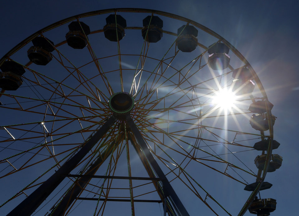 Photo - The Ferris wheel is silhouetted by the sun during the last day of the Oklahoma State Fair in Oklahoma City, Sunday, Sept. 22, 2013. Photo by Sarah Phipps, The Oklahoman