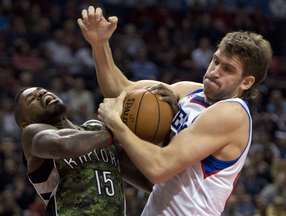 Toronto Raptors forward Amir Johnson, left, has the ball stripped by Philadelphia 76ers forward Spencer Hawes while driving to the hoop during first-half NBA basketball action action in Toronto, Saturday, Nov. 10, 2012. (AP Photo/The Canadian Press, Frank Gunn)
