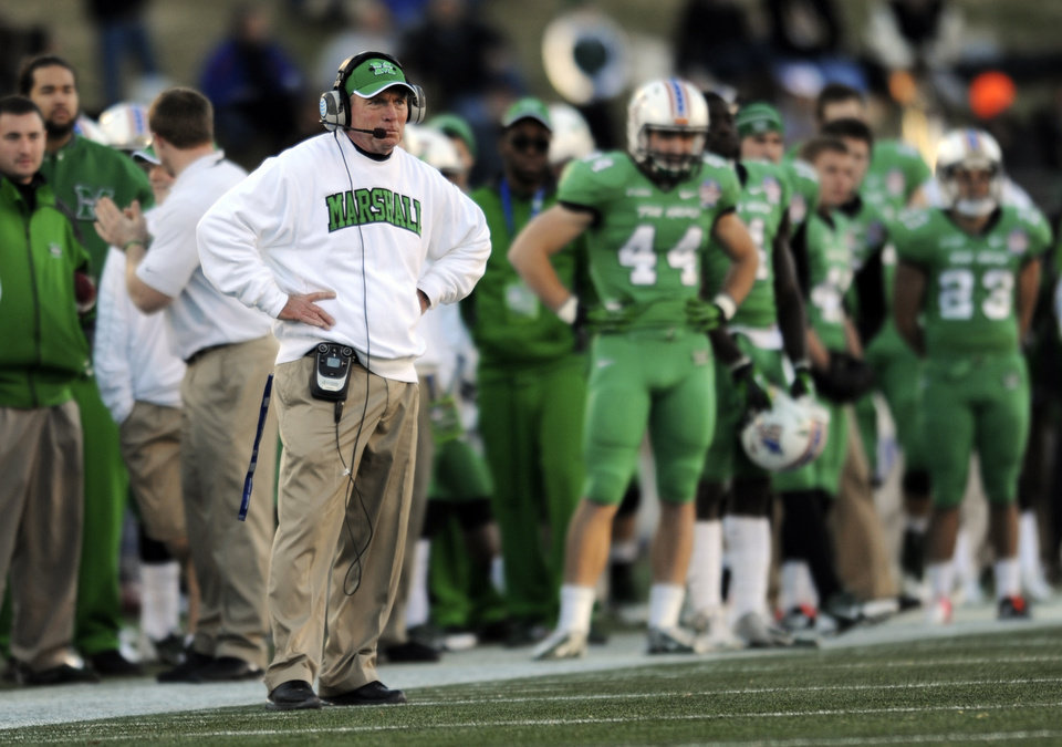 Photo - FILE - In this Dec. 27, 2013, file photo, Marshall's head coach Doc Holliday watches from the sideline in the first half of the Military Bowl against Marshall in Annapolis, Md. Now that Chris Petersen has left Boise State for Washington, college football needs another coach from outside the so-called Big 5 conferences that will have his name come up for almost every big job. (AP Photo/Gail Burton, File)