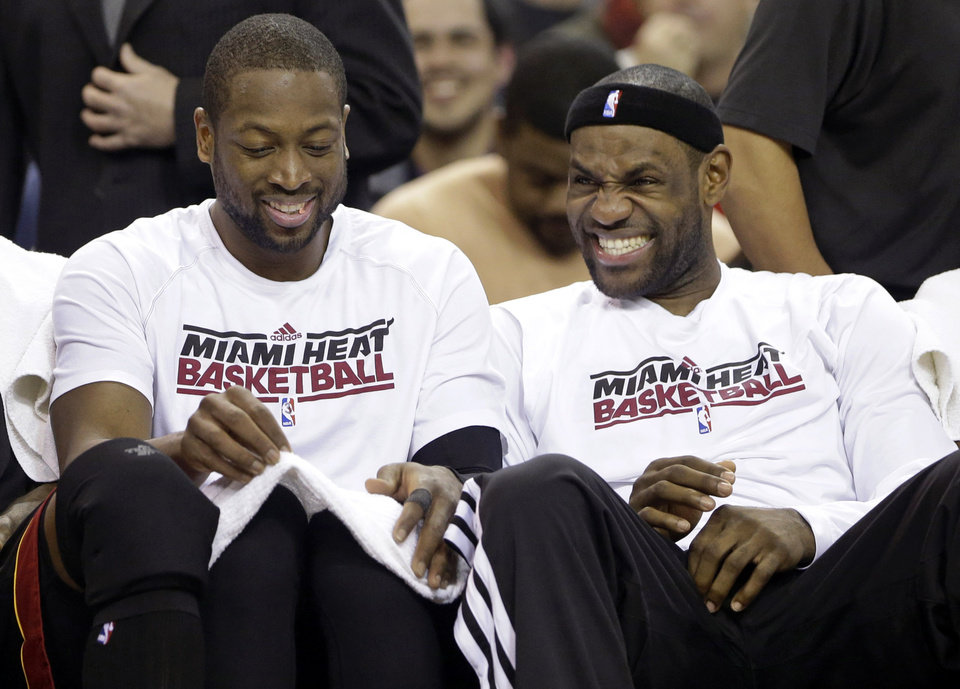 Miami Heat's Dwayne Wade,left, and LeBron James sit together on the bench in the closing moments of their NBA basketball game against the Sacramento Kings in Sacramento, Calif., Saturday, Jan. 12, 2013.  The Heat won 128-99. (AP Photo/Rich Pedroncelli)