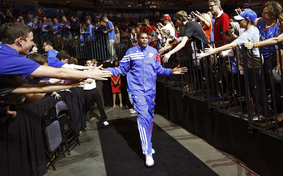 Photo - Oklahoma City's Kevin Durant slaps hands with fans as he runs to the court before the NBA basketball game between the Oklahoma City Thunder and the Los Angeles Clippers at Chesapeake Energy Arena in Oklahoma City, Wednesday, April 11, 2012. Photo by Bryan Terry, The Oklahoman
