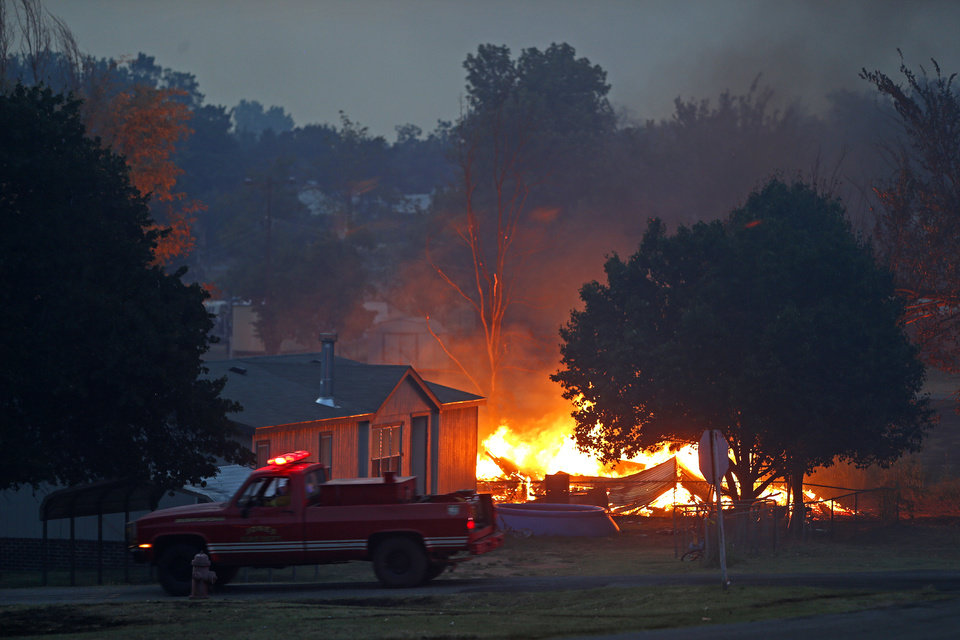 Photo - An emergency vehicle drives past a burning home in Luther, Okla., after wildfire moved through the area on Friday, August 3, 2012. Photo by Bryan Terry, The Oklahoman