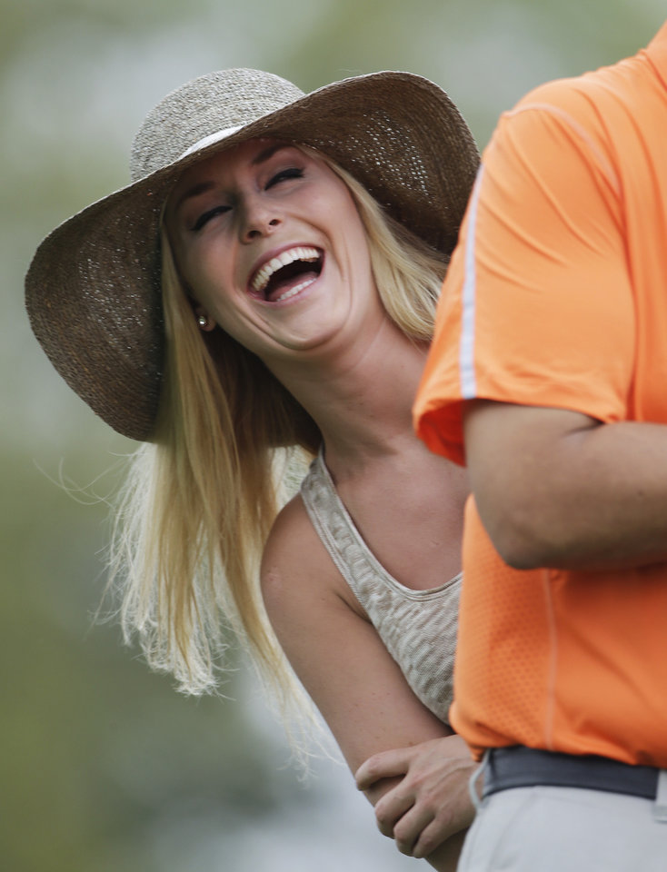 Photo - Skier Lindsey Vonn laughs while watching Tiger Woods during the first round of the Masters golf tournament Thursday, April 11, 2013, in Augusta, Ga. (AP Photo/Darron Cummings)