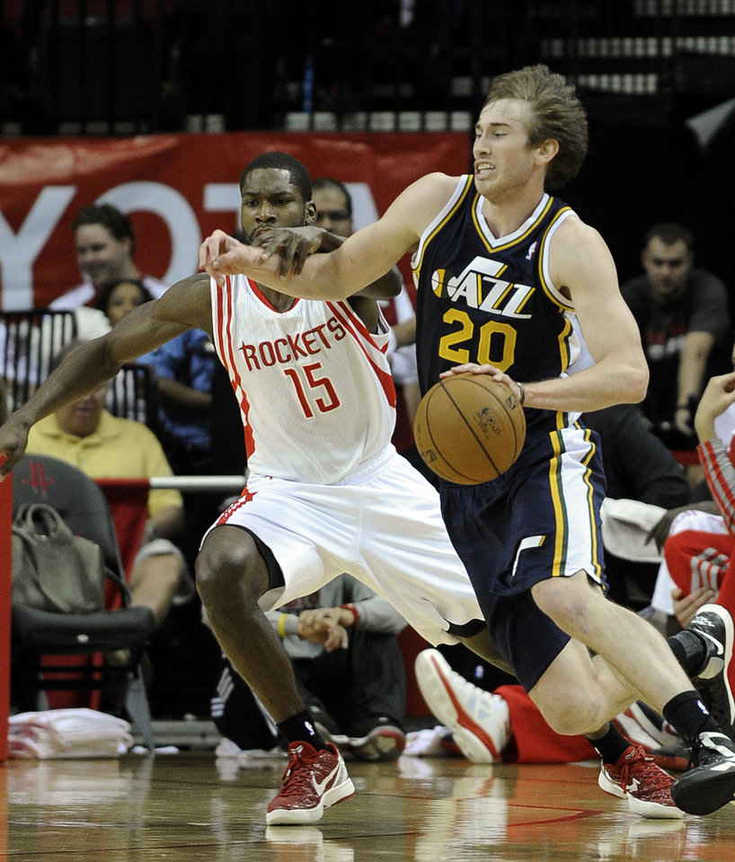 Photo - Utah Jazz's Gordon Hayward (20) tries to drive the ball past Houston Rockets' Toney Douglas (15) in the first half of an NBA basketball game on Saturday, Dec. 1, 2012, in Houston. (AP Photo/Pat Sullivan)