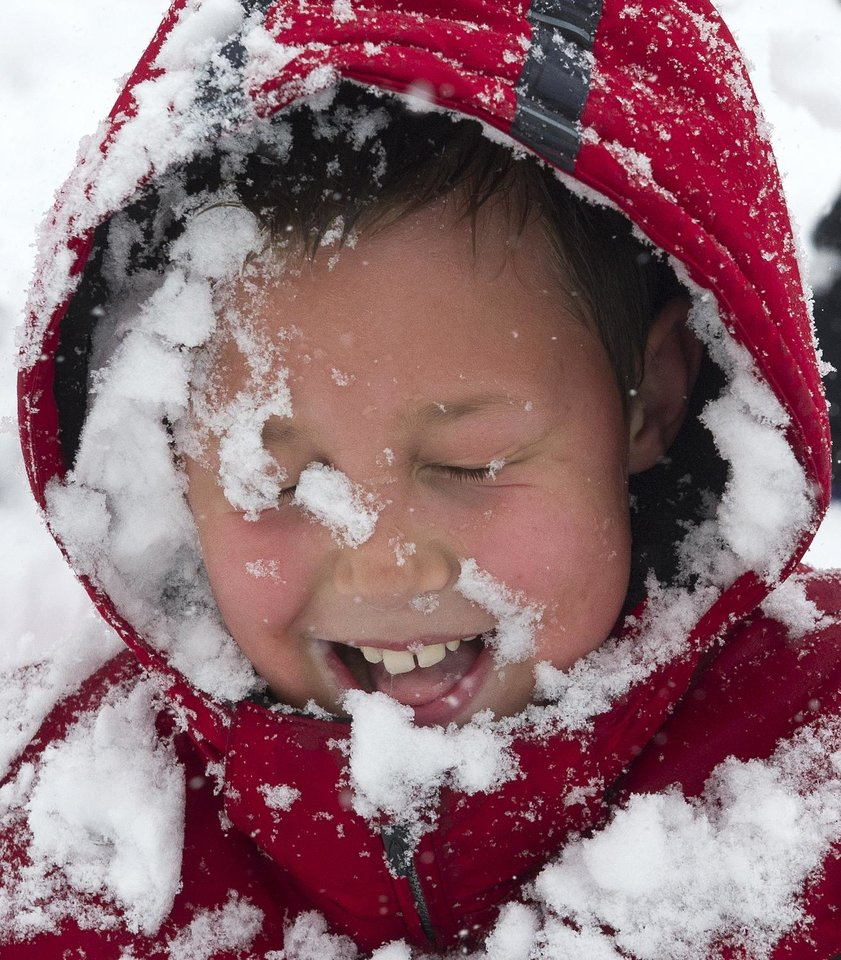 Photo - Cameron Willson, 10, has a faceful of snow after being hit with a snowball Monday morning March 25, 2013 during a neighborhood snowball fight   in Fort Wayne, Indiana.  (AP Photo/The Journal Gazette, Swikar Patel)  NEWS-SENTINEL OUT; MANDATORY CREDIT; NO SALES; MAGS OUT