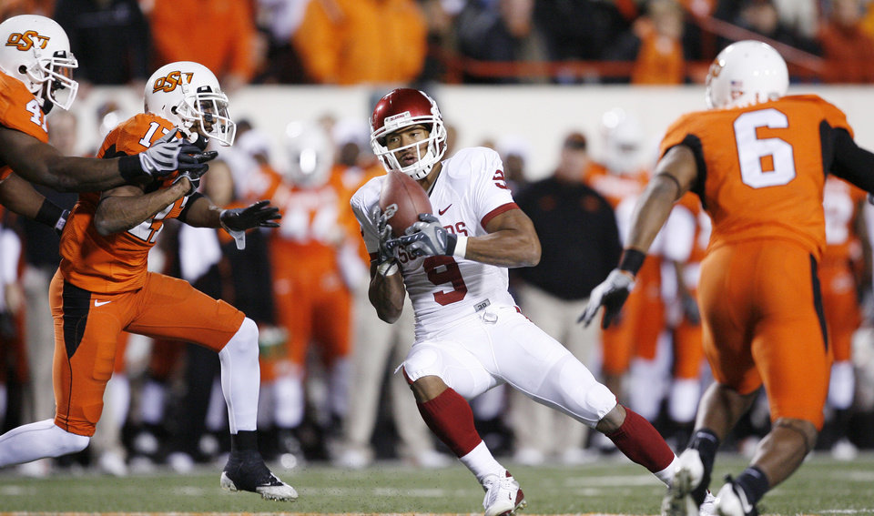 OU's Brandon Caleb catches pass in the middle of Cowboys during the first half of the college football game between the University of Oklahoma Sooners (OU) and Oklahoma State University Cowboys (OSU) at Boone Pickens Stadium on Saturday, Nov. 29, 2008, in Stillwater, Okla. STAFF PHOTO BY BRYAN TERRY