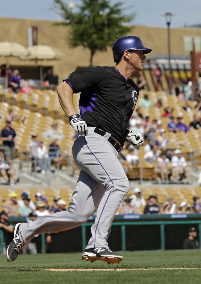 Photo - Colorado Rockies' DJ LeMahieu rounds first on a triple in the third inning of a spring exhibition baseball game against the Chicago White Sox Tuesday, March 25, 2014, in Glendale, Ariz. (AP Photo/Mark Duncan)