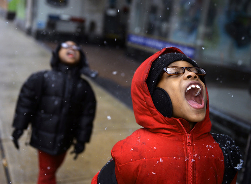 Photo - Ashawn Creque, 6, right, catches snowflakes on his tongue as his brother Amari Brady, 5, follows on their way home from a clinic on Thursday, Jan. 2, 2014, in York, Pa. Northern and eastern Pennsylvania saw 6 to 8 inches of snow, while southern and western Pennsylvania saw 2 to 5 inches, the National Weather Service said Friday. (AP Photo/York Daily Record, Chris Dunn) YORK DISPATCH OUT