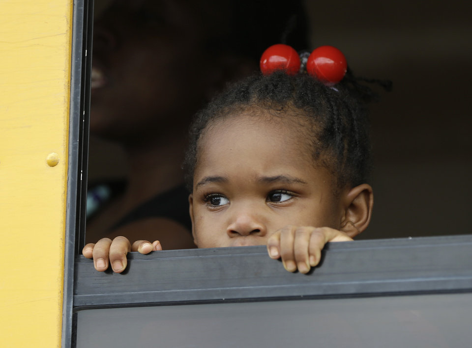 Photo - A child peers out the window of a school bus as busses arrive with students after an incident at Ronald McNair Discovery Learning Academy, Tuesday, Aug. 20, 2013 in Decatur, Ga.  Superintendent Michael Thurmond says all students at Ronald E. McNair Discovery Learning Academy in Decatur east of Atlanta are accounted for and safe Tuesday and that he is not aware of any injuries. (AP Photo/John Bazemore)