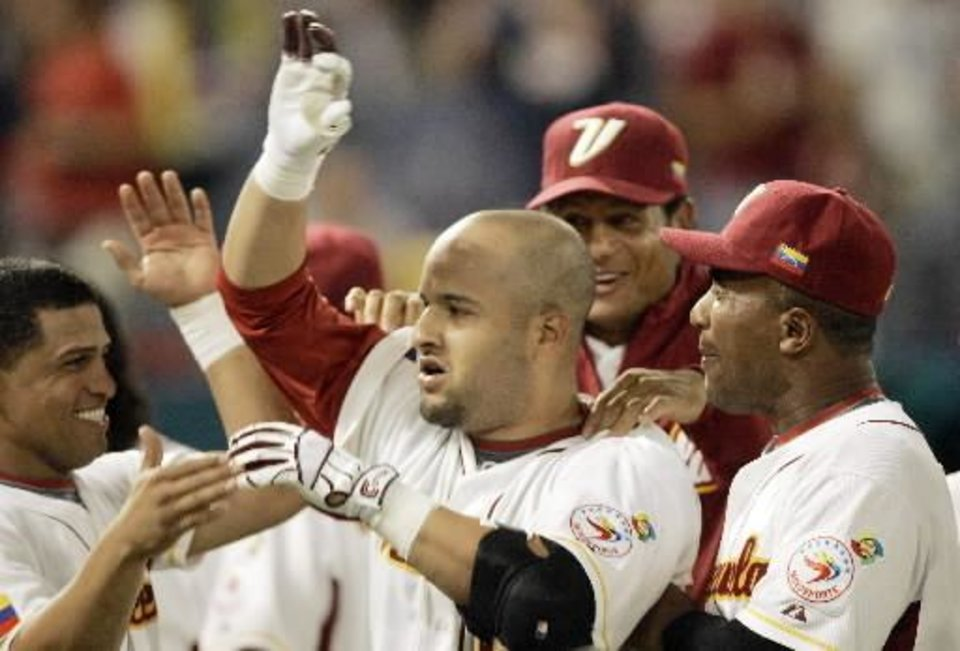 Photo - Venezuela's  Max  Ramirez, center, is congratulated by teammates Cesar Izturis, left, Bobby Abreu, second from right, and Mellvin Mora, right, after hitting a three-run home run and driving in Miguel Cabrera and Gerardo Parra, against the United States in the sixth inning of the World Baseball Classic in Miami, Wednesday, March 18, 2009. Venezuela won 10-6. (AP Photo/Alan Diaz)
