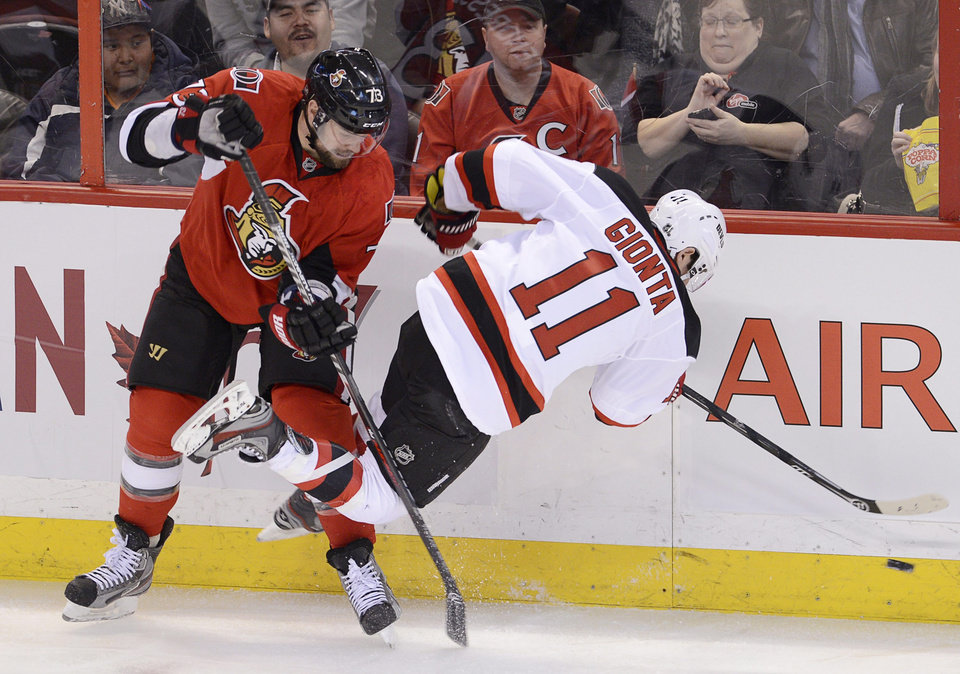 Photo - Ottawa Senators left wing Guillaume Latendresse, left, collides with New Jersey Devils right wing Stephen Gionta during first period NHL action in Ottawa, on Monday March 25, 2013.  (AP Photo/The Canadian Press, Adrian Wyld)