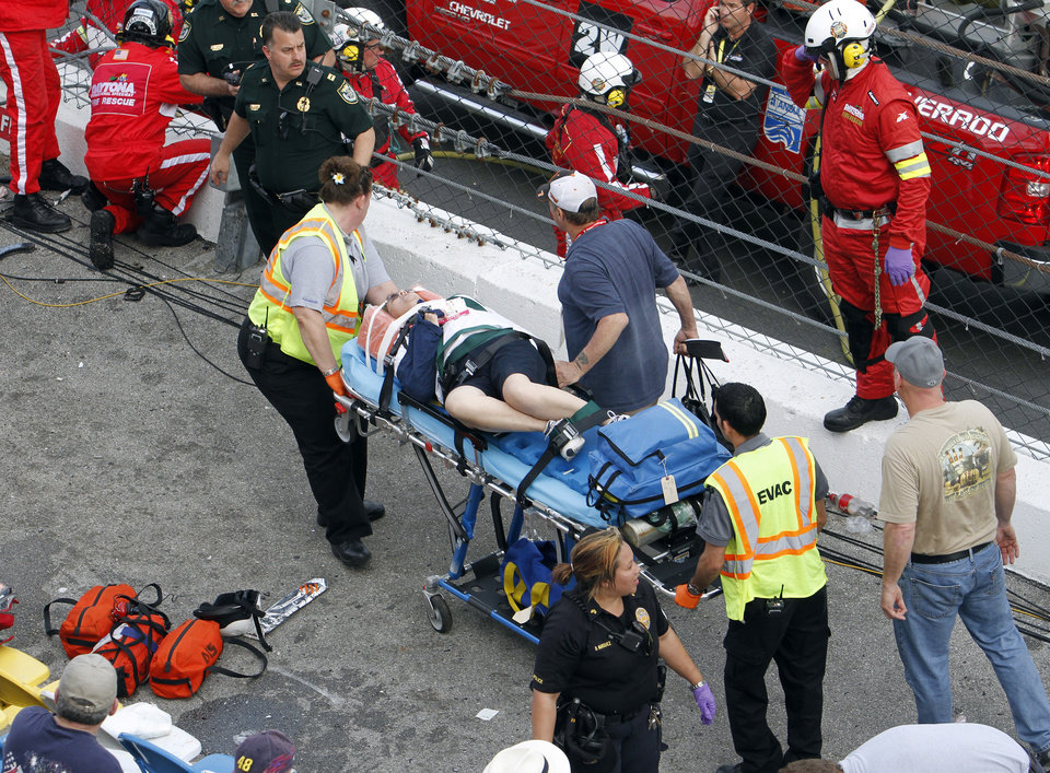 An injured spectator is treated after a crash at the conclusion of the NASCAR Nationwide Series auto race Saturday, Feb. 23, 2013, at Daytona International Speedway in Daytona Beach, Fla. Driver Kyle Larson\'s car hit the safety fence sending car parts and other debris flying into the stands. (AP Photo/David Graham)