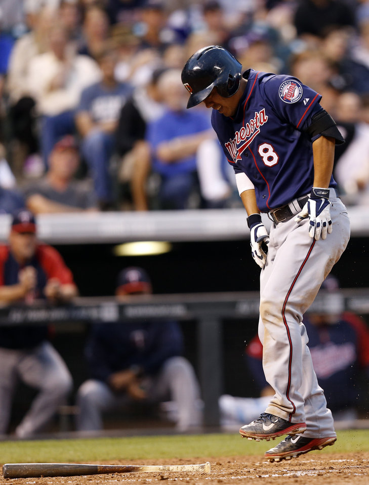 Photo - Minnesota Twins' Kurt Suzuki reacts after hitting a foul ball off against the Colorado Rockies during the fifth inning of a baseball game on Friday, July 11, 2014, in Denver. (AP Photo/Jack Dempsey)