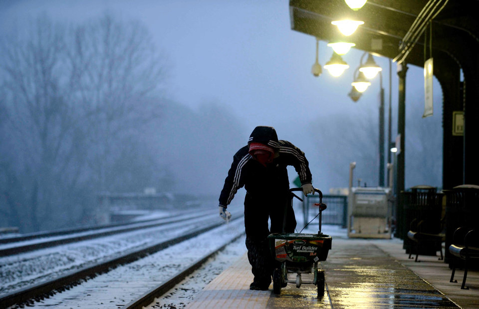 Photo - John McKeown walks to pick up his vehicle on Tuesday, Jan. 21, 2014, in Stafford, Va. The winter storm blowing into Virginia is expected to dump up to 10 inches of snow in some areas. (AP Photo/The Free Lance-Star, Reza A. Marvashti)
