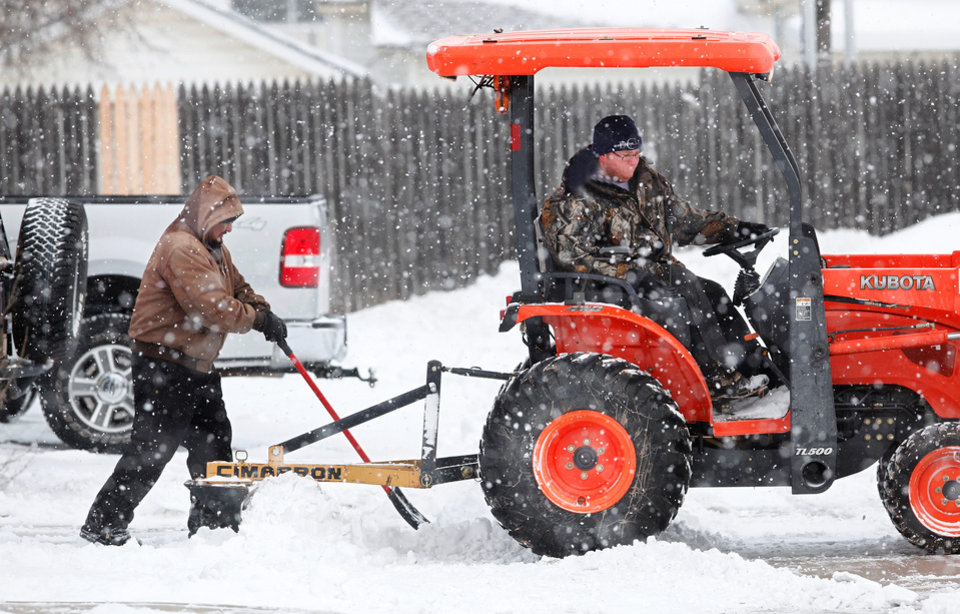 Photo - Men use a tractor and shovels to clear snow from the parking lot of this restaurant on Air Depot in Midwest City.  A second winter storm in a week dumped about 6 inches of snow in the Oklahoma City area Tuesday morning, Feb. 9, 2011.   Photo by Jim Beckel, The Oklahoman