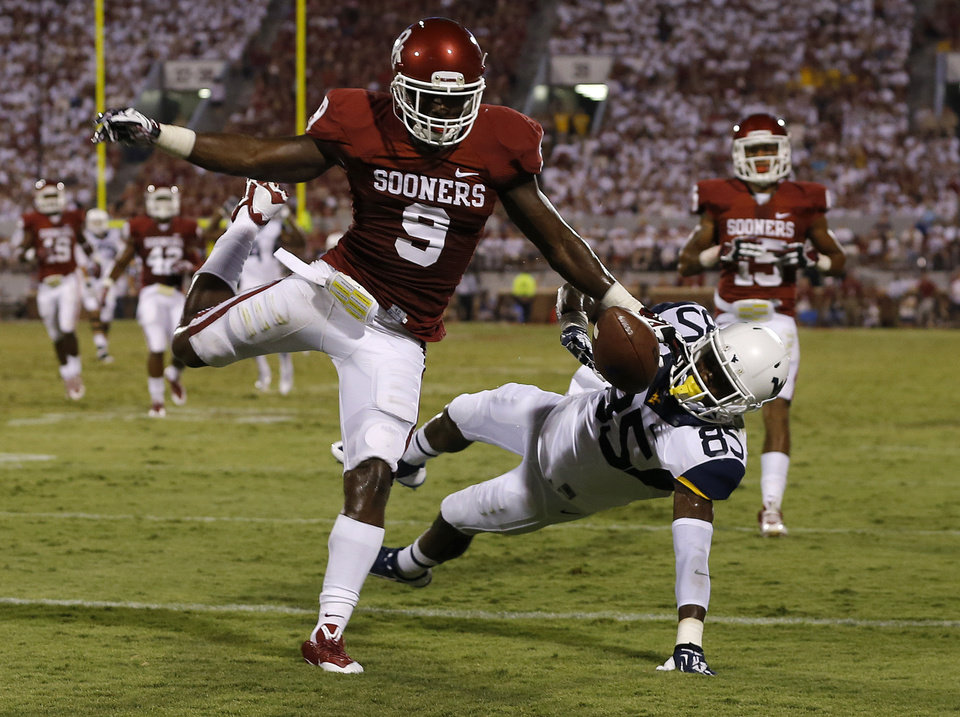 Photo - Oklahoma's Gabe Lynn (9) breaks up a pass intended for West Virginia's Ivan McCartney (85) during a college football game between the University of Oklahoma Sooners (OU) and the West Virginia University Mountaineers at Gaylord Family-Oklahoma Memorial Stadium in Norman, Okla., on Saturday, Sept. 7, 2013. Oklahoma won 16-7. Photo by Bryan Terry, The Oklahoman