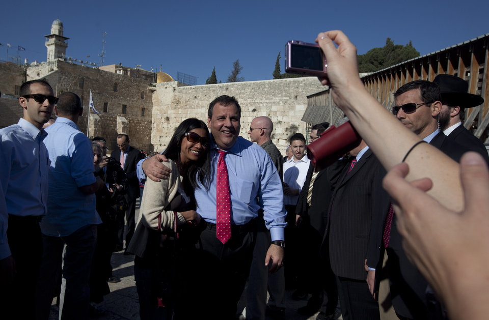 Photo -   A tourist has her picture taken with New Jersey Gov. Chris Christie, center, during his visit to the Western Wall, the holiest site where Jews can pray, in Jerusalem's old city Monday, April 2, 2012. Christie kicked off his first official overseas trip Monday meeting Israel's leader in a visit that may boost the rising Republican star's foreign policy credentials ahead of November's presidential election. (AP Photo/Sebastian Scheiner)