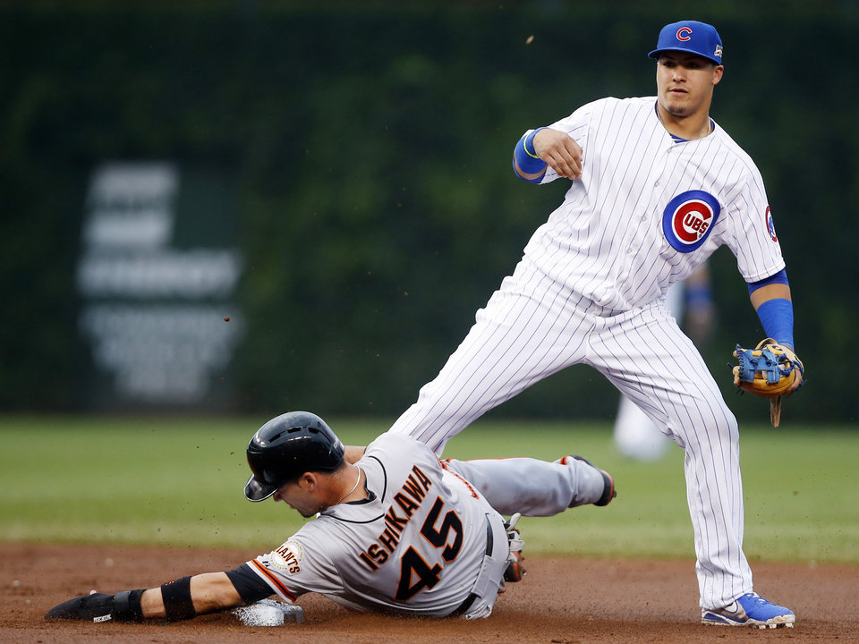 Photo - San Francisco Giants' Travis Ishikawa (45) is forced out by Chicago Cubs shortstop Javier Baez on a single hit by Angel Pagan during the seventh inning of the continuation of a rain-suspended baseball game that began Tuesday, on Thursday, Aug. 21, 2014, in Chicago. (AP Photo/Andrew A. Nelles)
