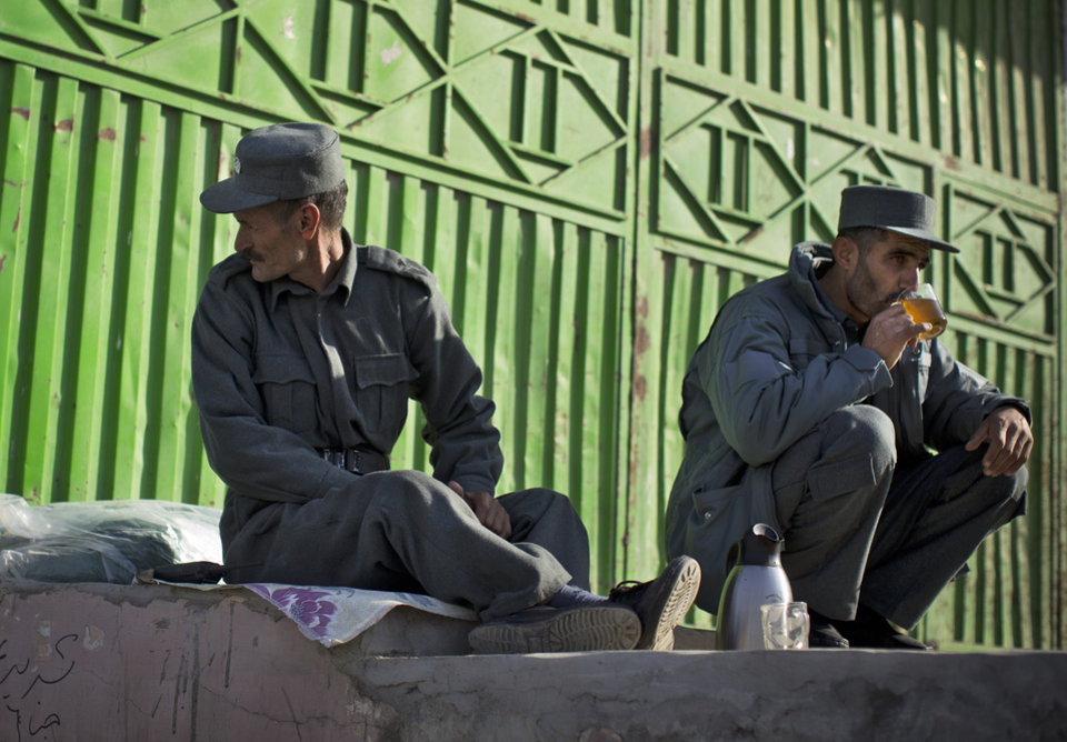 Photo - Afghan policemen enjoy a cup of tea at their checkpoint outside the venue where thousands of prominent Afghans gather to debate a contentious security agreement with the United States in Kabul, Afghanistan, Thursday, Nov. 21, 2013. Afghanistan's president Hamid Karzai said he backs a security deal with the United States but told the gathering of elders that if they and parliament approve the agreement it should be signed after next spring's elections. Without the agreement the United States previously warned that it will remove all its troops by the end of 2014.  (AP Photo/Anja Niedringhaus)