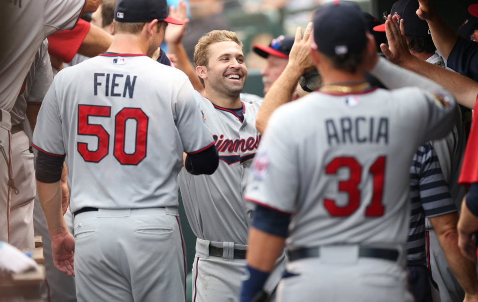 Photo - Minnesota Twins' Brian Dozier, center, is congratulated after his three-run home run by teammates Casey Fein, left, and Oswaldo Arcia against the Colorado Rockies in the ninth inning of the Twins' 13-5 victory in an interleague baseball game in Denver on Sunday, July 13, 2014. (AP Photo/David Zalubowski)