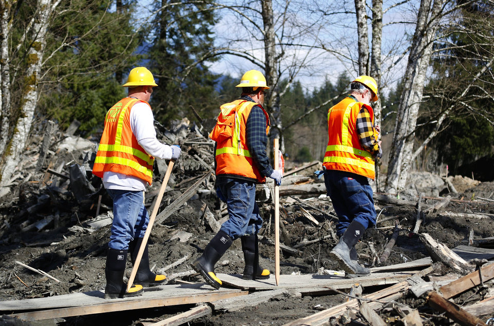 Photo - Washington State Department of Transportation workers enter the mudslide site on a constructed path of plywood on Highway 530 near mile marker 37, near Oso, Wash., Tuesday, April 1, 2014. The death toll from the March 22 mudslide has increased to 28. (AP Photo/The Seattle Times, Lindsey Wasson)  SEATTLE OUT; USA TODAY OUT; MAGS OUT; TELEVISION OUT; NO SALES; MANDATORY CREDIT TO BOTH THE SEATTLE TIMES AND THE PHOTOGRAPHER