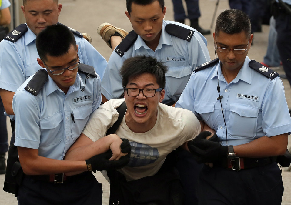 Photo - A protester, center, is taken away by police officers after hundreds of protesters staged a peaceful sit-ins overnight on a street in the financial district in Hong Kong Wednesday, July 2, 2014, following a huge rally to show their support for democratic reform and oppose Beijing's desire to have the final say on candidates for the chief executive's job. (AP Photo/Vincent Yu)