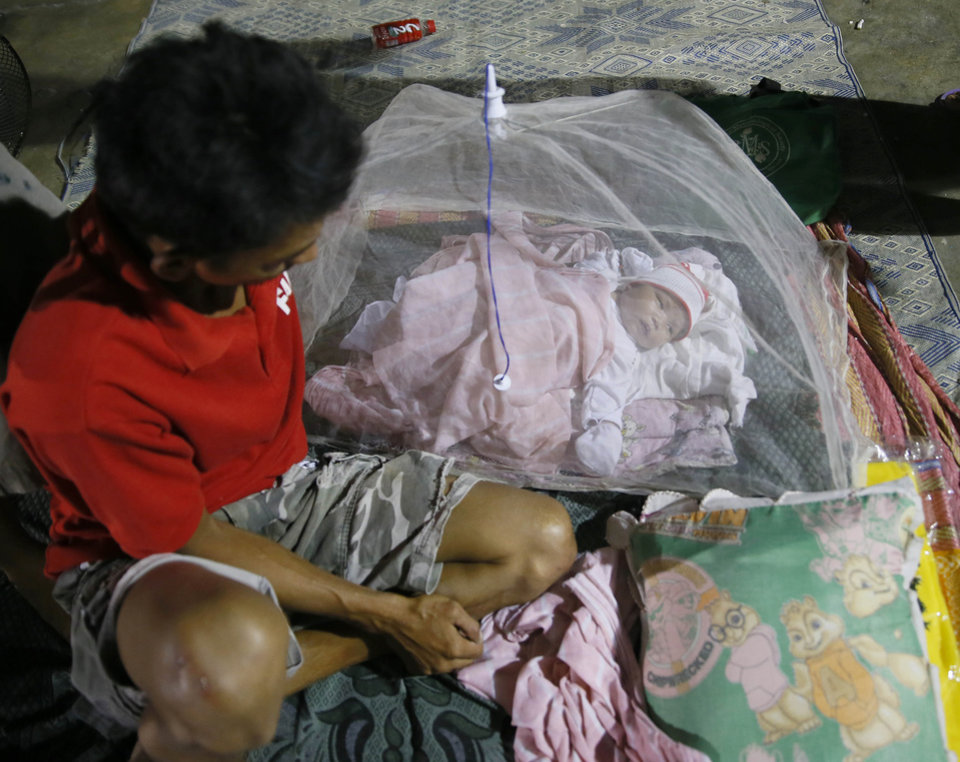 Photo - Typhoon evacuee Julius Pacula tends to his 16-day-old baby Yumi Anne inside a school gymnasium which serves as an evacuation center following the onslaught of Typhoon Koppu in Cabanatuan city in northern Philippines Monday, Oct. 19, 2015. The slow-moving typhoon blew ashore with fierce wind in the northeastern Philippines early Sunday, toppling trees and knocking out power and communications and forcing the evacuation of thousands of villagers. (AP Photo/Bullit Marquez)