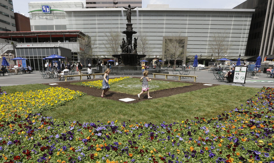 Photo - This April 10, 2013 photo shows Hannah Bailey, left, running the bases with sister Eva Bailey on a baseball diamond floral display set up on Fountain Square in Cincinnati. The heart of downtown Cincinnati, Fountain Square underwent a $49 million renovation and reopened in 2006. (AP Photo/Al Behrman)