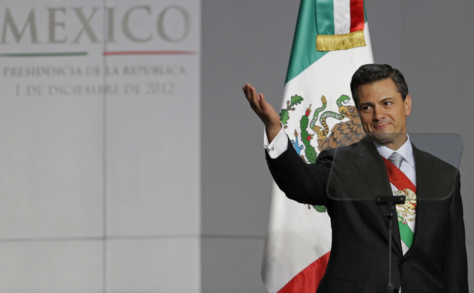 Mexico's newly sworn-in President Enrique Pena Nieto acknowledges the applause of the crowd as he arrives at the National Palace to deliver his inaugural speech in Mexico City, Saturday, Dec. 1, 2012. Protesters opposed to the new president clashed with tear gas-wielding police early Saturday morning outside the National Congress, where Pena Nieto took the oath of office. (AP Photo/Andres Leighton)