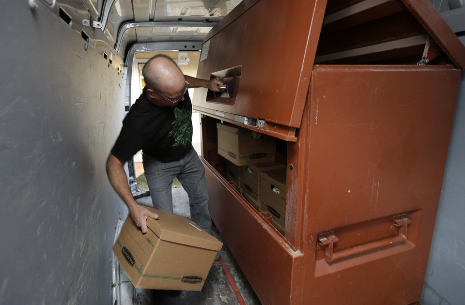 Photo - In this July 8, 2014, photo, Phil Tobias, director of Sea of Green Farms, loads boxes of recreational marijuana into a lockbox inside a delivery van in Seattle before leaving to take the product to a store in Bellingham, Wash. It was the first delivery for the company since retail licenses were issued by the state on Monday, July 7. (AP Photo/Ted S. Warren)
