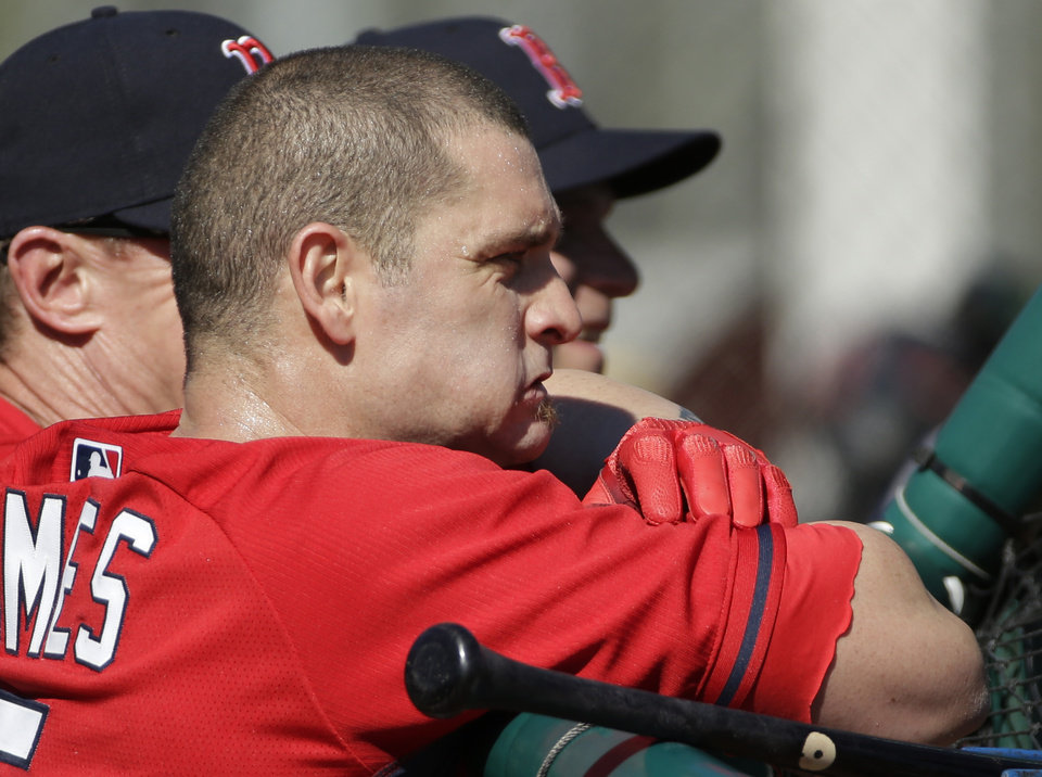 Photo - Boston Red Sox left fielder Jonny Gomes watches from behind the batting cage during spring training baseball practice Tuesday, Feb. 18, 2014, in Fort Myers, Fla. (AP Photo/Steven Senne)