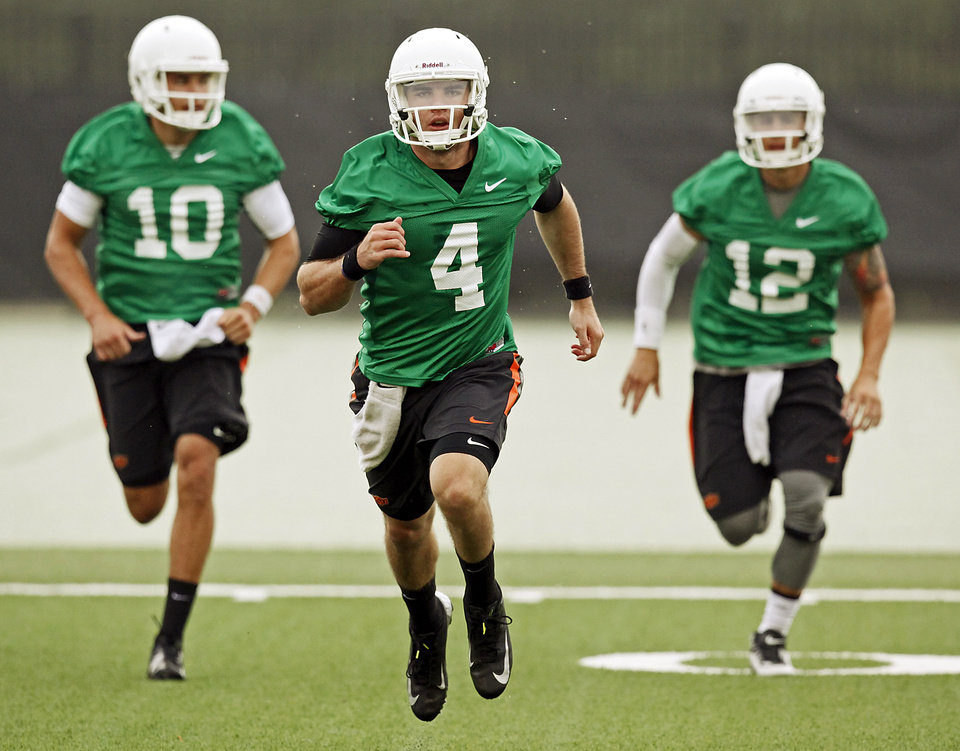 Photo - Oklahoma State quarterback J.W. Walsh (4) runs ahead of fellow quarterbacks Mason Rudolph (10) and Daxx Garman (12) during the first team practice of the fall at the Sherman E. Smith Training Facility on the campus of Oklahoma State University in Stillwater on August 1, 2014. Photo by KT King, The Oklahoman