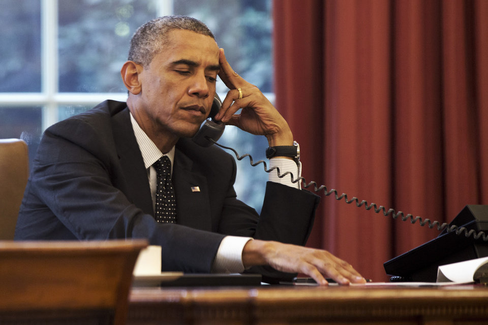 Photo - President Barack Obama listens during a phone call with Jordan's King Abdullah II Jordan, according to the White House, Friday, Aug. 8, 2014, in the Oval Office of the White House in Washington. (AP Photo/Jacquelyn Martin)