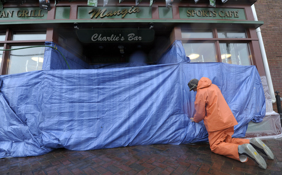 Charlie Priola, owner of Mangia Italian Grill and Sports Cafe in Annapolis, Md., protects his restaurant before Hurricane Sandy arrives in Annapolis, Monday, Oct. 29, 2012. (AP Photo/Susan Walsh) ORG XMIT: MDSW101