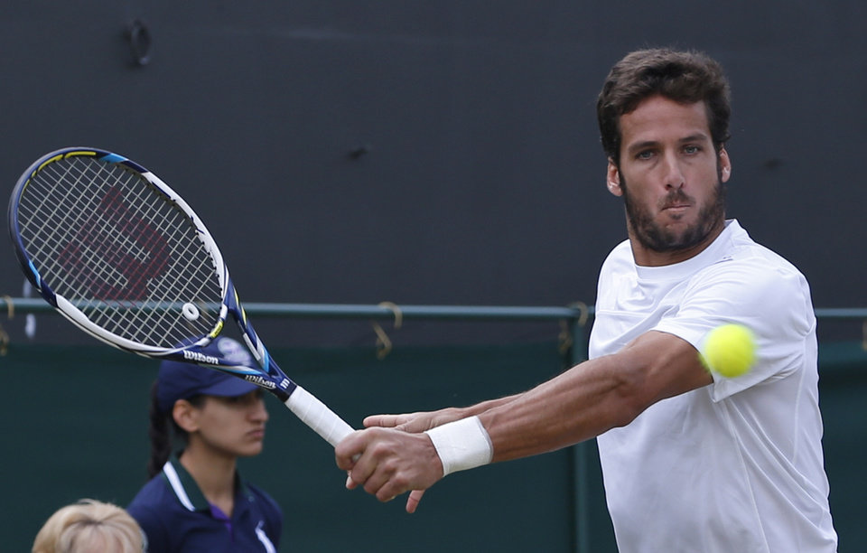 Photo - Feliciano Lopez of Spain plays a return to John Isner of the U.S. during their men's singles match at the All England Lawn Tennis Championships in Wimbledon, London, Monday, June 30, 2014. (AP Photo/Pavel Golovkin)