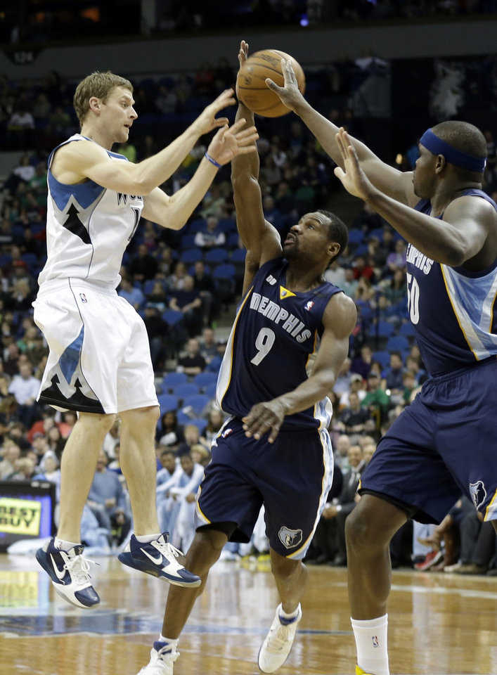 Photo - Minnesota Timberwolves' Luke Ridnour, left, makes a pass over Memphis Grizzlies' Tony Allen and Zach Randolph, right, in the first quarter of an NBA basketball game on Saturday, March 30, 2013, in Minneapolis. (AP Photo/Jim Mone)