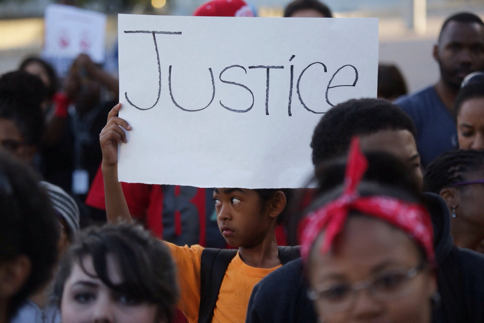 Photo - A child holds a sign during a vigil at Hart Plaza in downtown Detroit on Thursday, Aug.14, 2014,  for Michael Brown who was shot by a police officer in Ferguson, Mo. (AP Photo/Detroit Free Press, Ryan Garza)