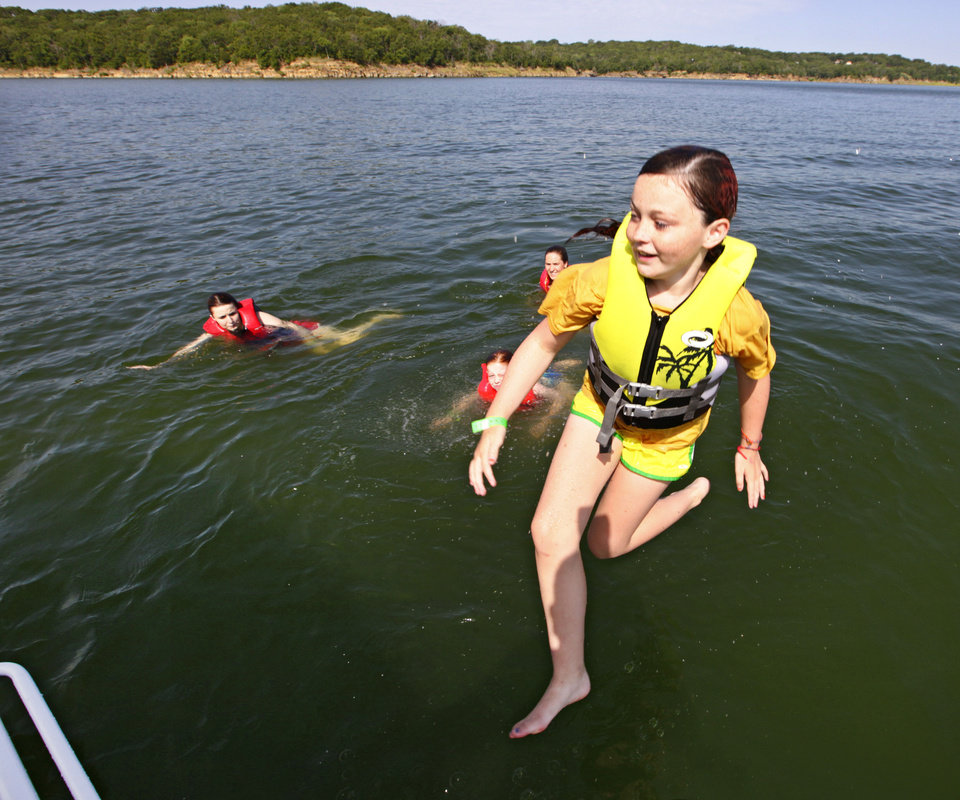 Photo - Izzy Mauldin , 11, jumps from the boat during Camp Cavett at Lake Texoma. After the fishing slowed, this boat moved to another area and some went swimming.   David McDaniel - The Oklahoman