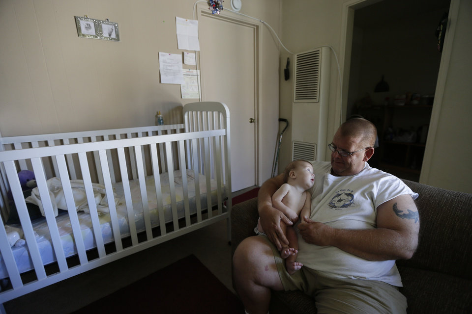 Photo -   In this Oct. 9, 2012 picture, veteran Arthur Lute holds his is 5-month-old son Evan in his one-bedroom apartment in Chula Vista, Calif. Lute's arduous journey from his days as a U.S. Marine to his nights sleeping on the streets illustrates the challenge the Obama administration faces to make good on its audacious promise: End homelessness among veterans by 2015. (AP Photo/Gregory Bull)