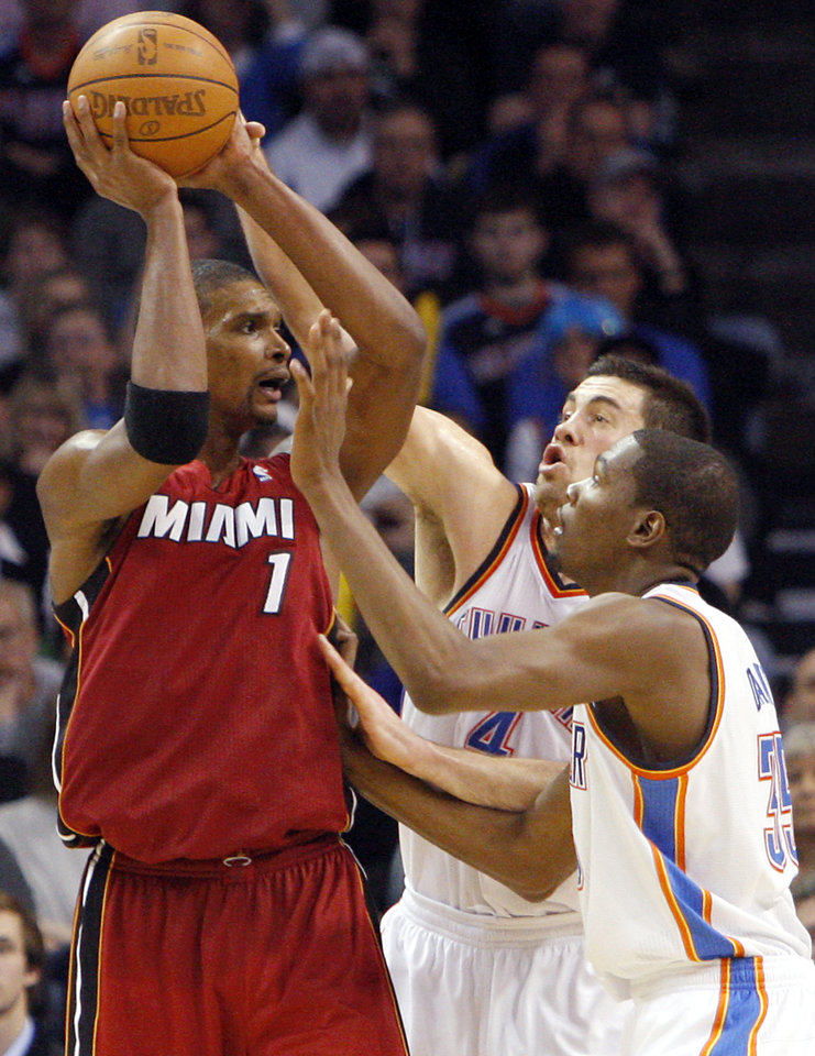 Photo - Oklahoma City's Kevin Durant and Nick Collison pressure Miami's Chris Bosh during their NBA basketball game at the OKC Arena in Oklahoma City on Thursday, Jan. 30, 2011. The Heat beat the Thunder 108-103. Photo by John Clanton, The Oklahoman