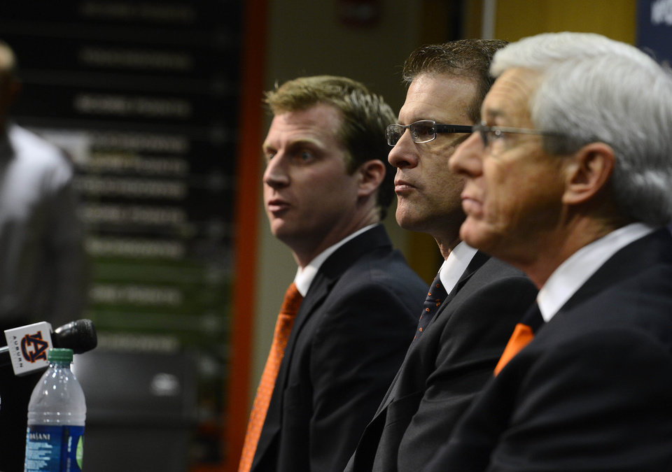 Photo - Auburn NCAA college footall coach Gus Malzahn, center, listens while his newly named defensive Ellis Johnson, right, and offensive coordinator Rhett Lashlee, left, speak during a press conference on Friday, Dec. 7, 2012 in Auburn, Ala.(AP Photo/Todd J. Van Emst)