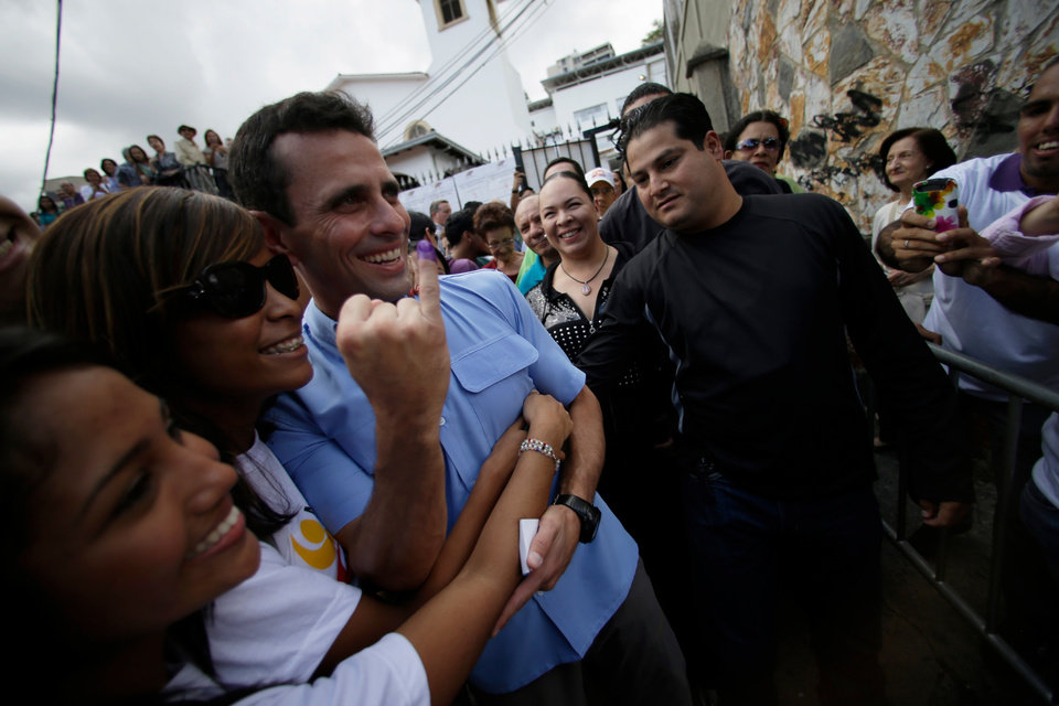Photo - Miranda's  Gov. Henrique Capriles, third from left, poses for pictures with supporters after casting his ballot at a polling station in Caracas, Venezuela, Sunday, Dec. 16, 2012. Venezuelans are choosing governors and state lawmakers  in elections that have become a key test of whether President Hugo Chavez's movement can endure if the socialist leader leaves the political stage. (AP Photo/Fernando Llano)