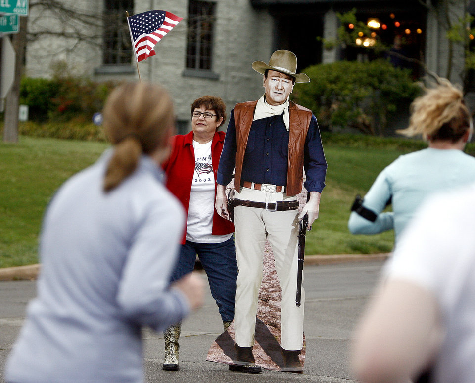 Martha Jett and John Wayne encourage runners up Shartel Ave. during the  8th annual Oklahoma City Memorial Marathon on Sunday, April 27, 2008, in Oklahoma City, Okla. Jett brought the John Wayne cutout to entertain runners.