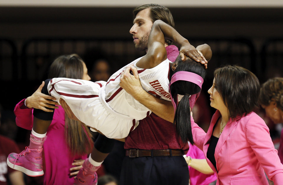Photo - Jozsef Szendrei, Oklahoma strength and conditioning coach, carries Aaryn Ellenberg (3) off the court next to athletic trainer Carolynn Loon after Ellenberg was injured in the second half during the women's Bedlam college basketball game between the OU Sooners and the OSU Cowgirls at Gallagher-Iba Arena in Stillwater, Okla., Sunday, Feb. 16, 2014. OSU won, 73-57. Photo by Nate Billings, The Oklahoman