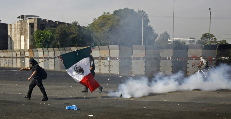 Photo - A demonstrator carrying a Mexican national flag walks past a cloud of tear gas during clashes with police outside the National Congress, just hours before Mexico's new president was to take the oath of office in Mexico City, Saturday, Dec. 1, 2012.  Hundreds of protesters  opposed to newly sworn-in President Enrique Pena Nieto banged on the steel security barriers around Congress, threw rocks, bottle rockets and firecrackers at police and yelled